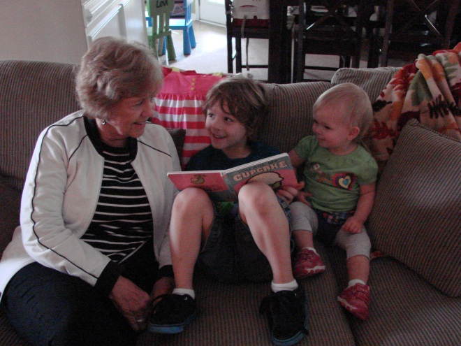 Brother reading a book to Grandma and Sis